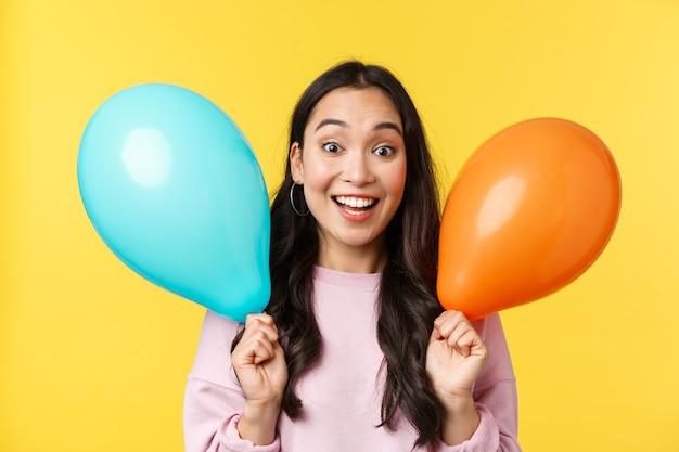 Emoções de pessoas, lazer do estilo de vida e conceito de beleza. alegre menina asiática feliz parabenizar com grande feriado, segurando dois balões e sorrindo amplamente, aproveite a festa sobre fundo amarelo.