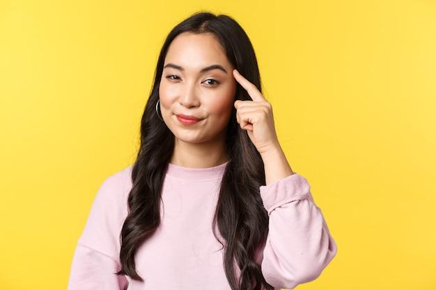 Emoções de pessoas, lazer do estilo de vida e conceito de beleza. close-up de menina asiática inteligente e criativa toque no templo, perguntando, pense, use seu cérebro, dando sugestão ou ideia interessante, fundo amarelo.