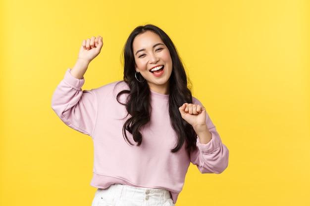 Emoções de pessoas, lazer do estilo de vida e conceito de beleza. menina asiática feliz e alegre, animada, dançando e se divertindo, festejando, tocando música ritmada e sorrindo sobre fundo amarelo