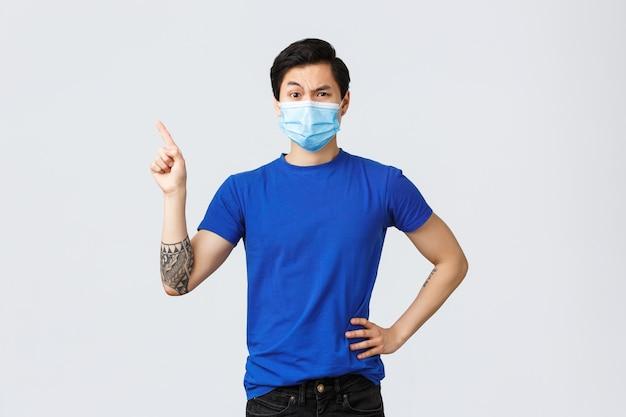 Emoções diferentes, distanciamento social, auto-quarentena no conceito de coronavírus e estilo de vida. homem asiático cético parecendo descrente, apontando o dedo no canto superior esquerdo, sendo desconfiado e indeciso