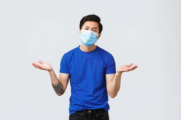 Emoções diferentes, distanciamento social, auto-quarentena no conceito de coronavírus. indiferente e indiferente cara asiático na máscara médica perguntando o que, espalhar as mãos para os lados, encolher os ombros, não me importo