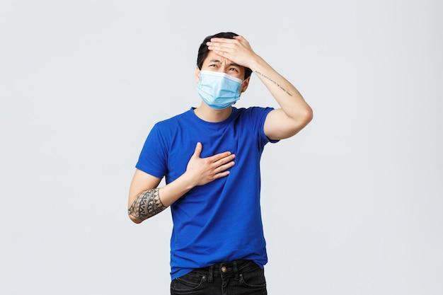 Emoções diferentes, distanciamento social, auto-quarentena no conceito de estilo de vida e coronavírus. doente jovem asiático com covid-19, tocando os pulmões ou coração e testa, tem febre alta, sintomas de gripe