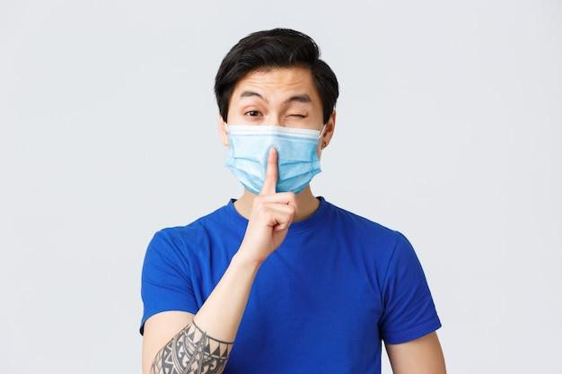Emoções diferentes, estilo de vida e lazer durante o coronavírus, conceito covid-19. homem asiático bonito atrevido na promessa de máscara médica manter segredo, calar e piscar coquete, ficar em silêncio