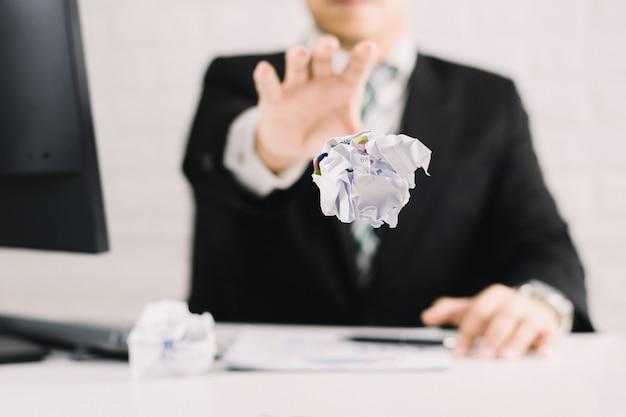 Emoções do empresário e conceito de falha amassado papel na mesa com, infeliz nenhuma idéia para pensar jogando papéis no escritório
