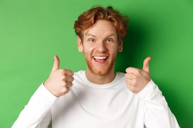 Emoções e conceito de moda. perto do homem ruivo alegre mostrando o polegar para cima e diga sim, aprove e goste de algo legal, fundo verde.
