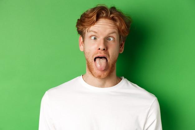 Emoções e conceito de moda. perto do homem ruivo engraçado mostrando caretas, enfiando a língua e apertando os olhos, em pé sobre um fundo verde.