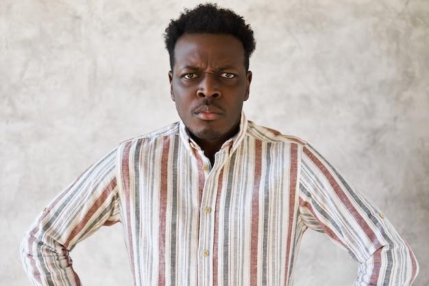 Emoções e reações humanas negativas. homem africano sombrio e taciturno, numa postura tensa com sobrancelhas franzidas