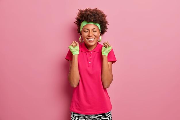 Emoções e sentimentos felizes. menina afro-americana sorridente com camiseta rosa, luvas esportivas e tiara, fecha os punhos de alegria, sente o gosto da vitória, comemora a vitória no concurso