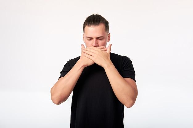 Emoções e sentimentos. retrato de um homem assustado com os olhos fechados cobrindo a boca com as mãos
