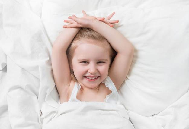 Emoções encantadoras da filha sorrindo na cama