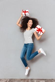 Emoções felizes da mulher positiva em camiseta listrada e calça jeans, desfrutando de muitos presentes, segurando nas mãos se divertindo festejando sobre parede cinza