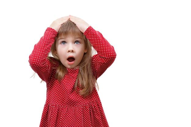 Emoções humanas. menina criança vestida de vermelho surpresa e chocada. mãos na cabeça, boca aberta.