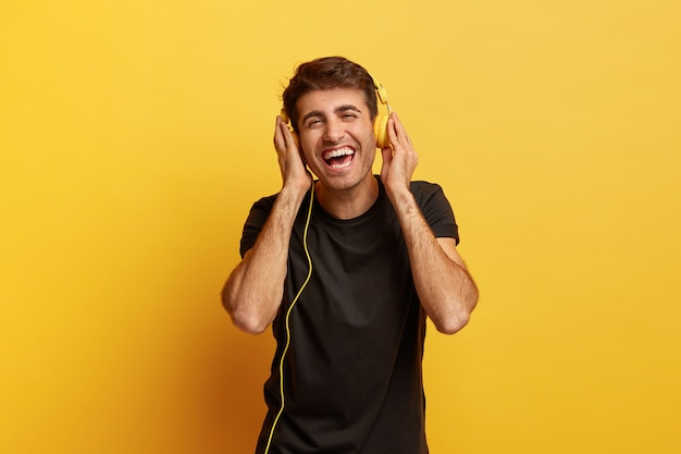 Emoções humanas positivas e conceito divertido. homem caucasiano alegre e feliz com fones de ouvido modernos e um sorriso largo