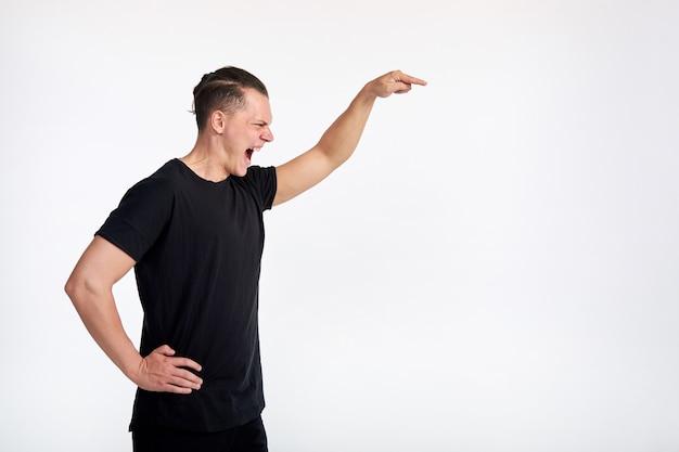 Emoções. linguagem corporal. dominação masculina. homem jovem agressivo e agressivo gritando e apontando para você