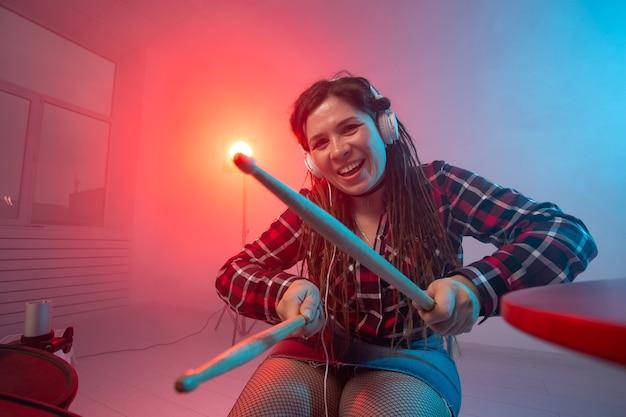 Emoções, música, hobbies e conceito de pessoas - jovem tocando bateria eletrônica em estúdio
