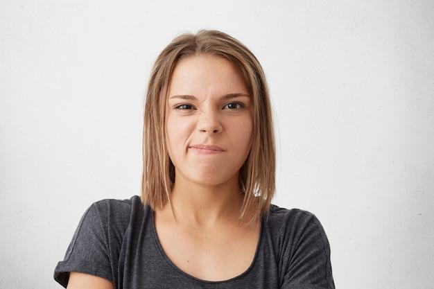 Emoções negativas, descontentamento. mulher irritada e ofendida curvando os lábios parecendo insatisfeita
