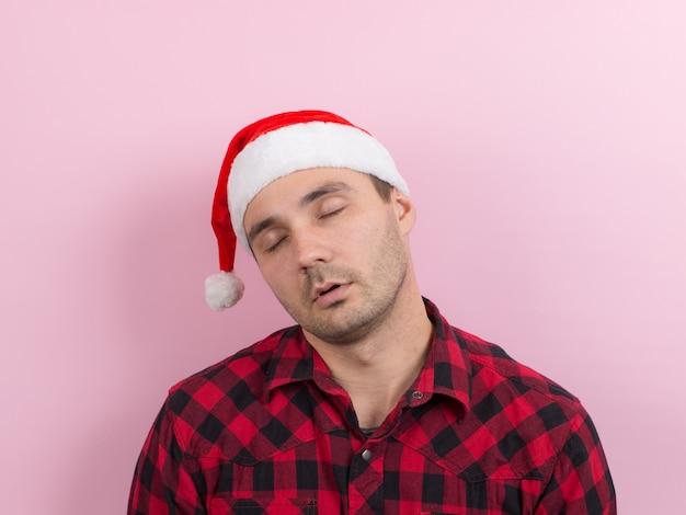 Emoções no rosto, cansado, ressaca de férias, consciência. um homem em um coelho xadrez e um chapéu vermelho de natal