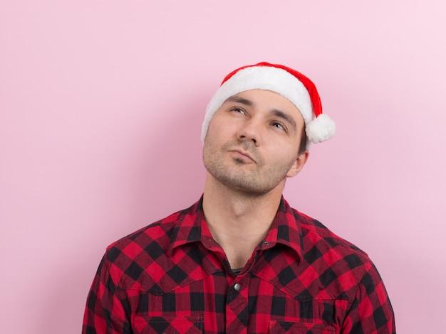 Emoções no rosto, pensativo, reflexão, plano, idéia. um homem em um coelho xadrez e um chapéu vermelho de natal