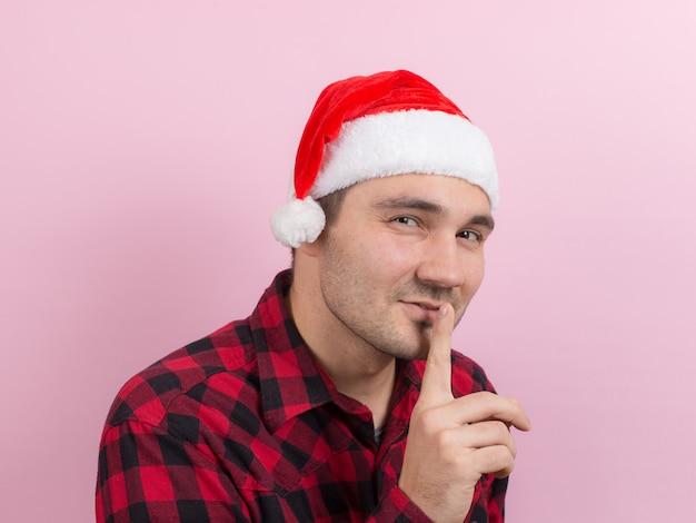 Emoções no rosto, zangado, ruim, bandido, tramando o mal. um homem em um coelho xadrez e um chapéu vermelho de natal