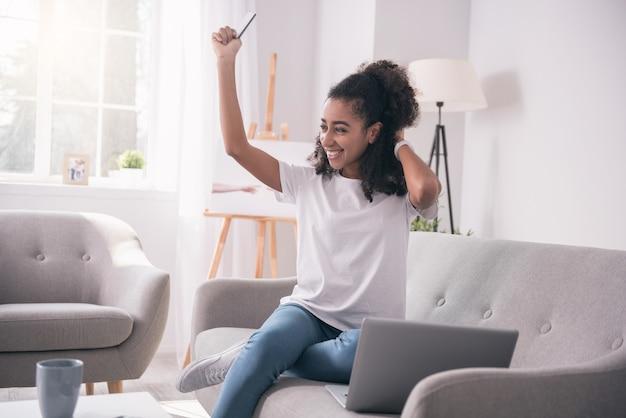 Emoções positivas. aluna alegre e simpática segurando seu cartão de crédito enquanto recebe sua primeira bolsa de estudos