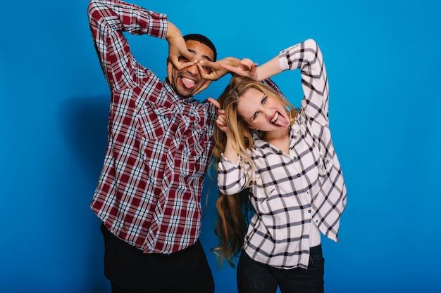 Emoções positivas brilhantes de retrato de casal animado engraçado brincando. divertindo-se, tempo livre, mostrando língua, alcaparra, macaco, engraçado