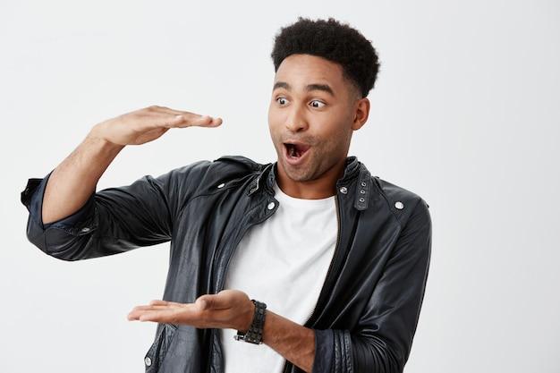 Emoções positivas. copie o espaço. retrato de jovem estudante masculino americano de pele bronzeada animado com cabelos cacheados em camiseta branca e jaqueta de couro gesticulando com as mãos, olhando de lado