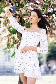 Emoções positivas de rosto em vestido branco de verão tirando fotos de self-retratos de selfies no smartphone