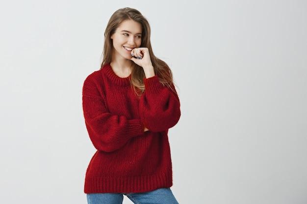 Emoções positivas e o conceito de pessoas. elegante aluna bonita camisola solta vermelha, segurando a mão no queixo enquanto sorrindo e olhando de lado com interesse e emoção, conversando com um amigo