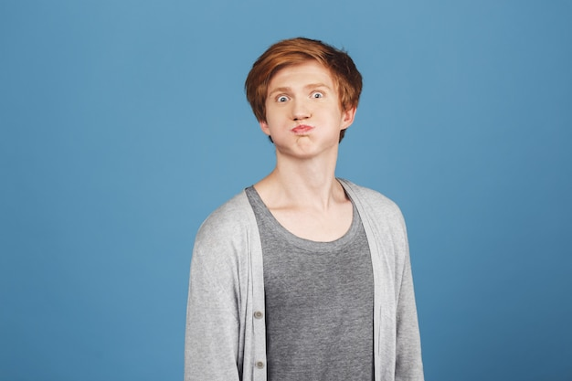 Emoções positivas. feche o retrato de jovem ruivo bonitão na elegante camiseta cinza sob casaco casual com expressão de rosto tolo, se divertindo.