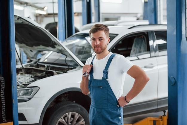 Emoções positivas. funcionário com uniforme azul trabalha no salão automóvel