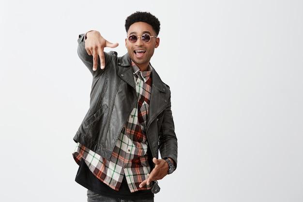 Emoções positivas. jovem bonito alegre de pele escura com penteado afro em elegante jaqueta de couro e óculos bronzeados, sorrindo brilhantemente, gesticulando com a mão