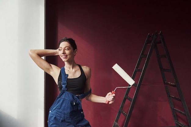 Emoções positivas. jovem dona de casa decidiu colar papel de parede em sua nova casa no quarto