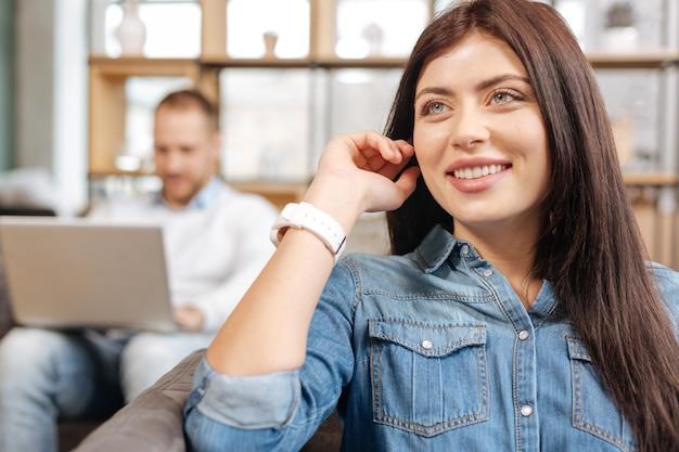 Emoções positivas. mulher atraente e encantada alegre sentada em seu escritório sorrindo enquanto está de ótimo humor