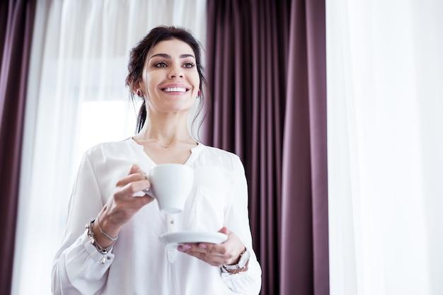 Emoções positivas. mulher de negócios inteligente encantada com um ótimo humor enquanto bebe seu café
