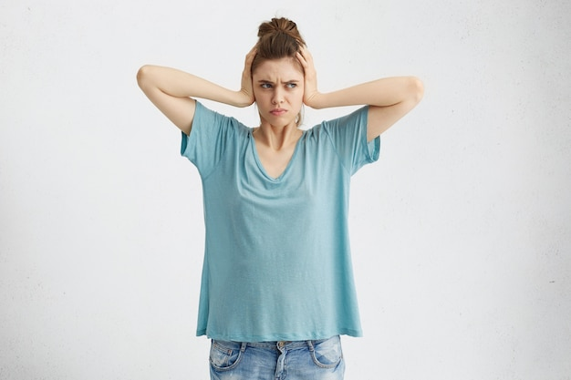 Emoções, reações e atitudes humanas negativas. mulher frustrada e irritada cobrindo os ouvidos com as mãos, irritada com barulho alto e irritante