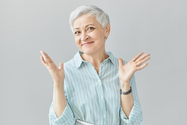 Emoções, reações e sentimentos humanos. foto de uma mulher européia feliz e muito feliz em um vestido azul listrado com um olhar confuso e sem noção, sorrindo timidamente e encolhendo os ombros, dizendo eu não sei
