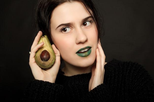 Emoções, saúde, pessoas, comida e conceito de beleza - retrato de uma mulher sorridente caucasiana atraente isolada no estúdio preto filmado com abacate