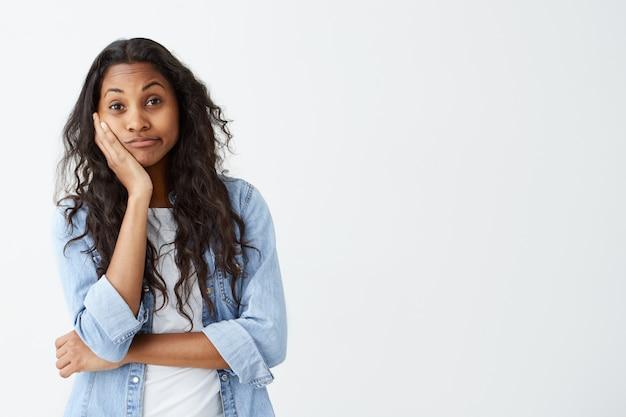 Emoções, sentimentos, reações e atitudes humanas. garota atraente de pele escura em camisa jeans com longos cabelos ondulados, mantendo a mão na bochecha em dúvida e suspeita, sentindo-se cético em relação a algo.
