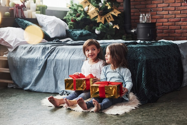 Emoções sinceras. férias de natal com presentes para essas duas crianças que estão sentadas dentro de casa no belo quarto perto da cama.