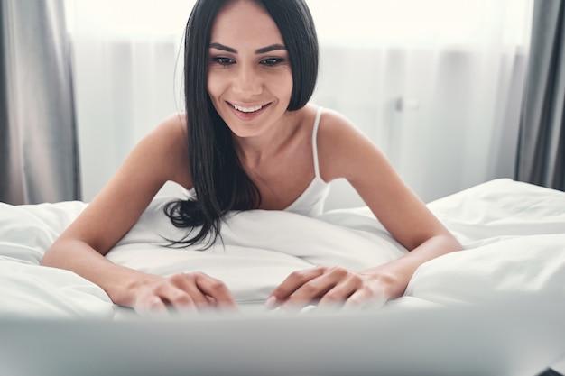 Emoções sinceras. mulher jovem feliz e positiva por estar em casa olhando para a tela do computador