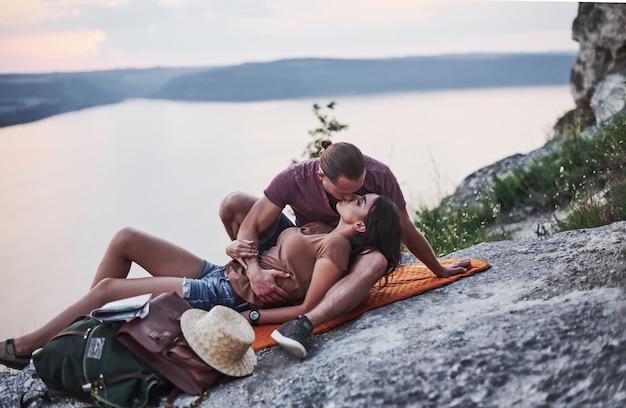 Emoções suaves. o jovem casal decidiu passar as férias de forma ativa na beira de uma linda rocha com um lago ao fundo.