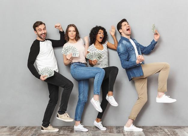 Emotionl animado grupo de amigos segurando dinheiro faz gesto de vencedor.