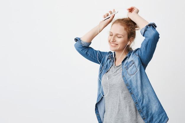 Emotiva adorável gengibre adolescente sorrindo enquanto ouve música através de fones de ouvido, segurando o smartphone e levantando as mãos na dança