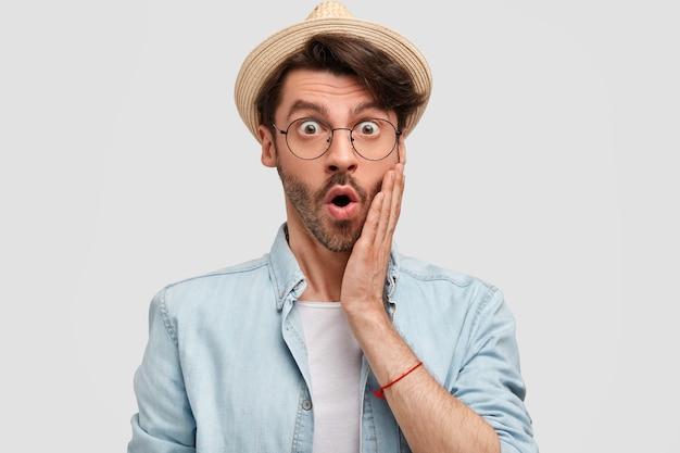 Emotiva chocada fazendeiro bem-sucedido vestindo uma camisa casual e chapéu de palha