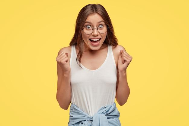 Emotiva, jovem europeia exultante exclama de entusiasmo, regozija-se com o negócio bem sucedido, celebra a vitória, vestida de forma casual