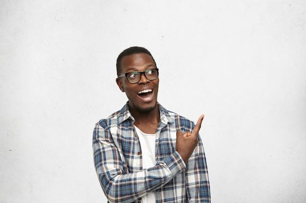 Emotivo emocional jovem afro-americano masculino usando óculos da moda, apontando o dedo indicador na parede branca em branco