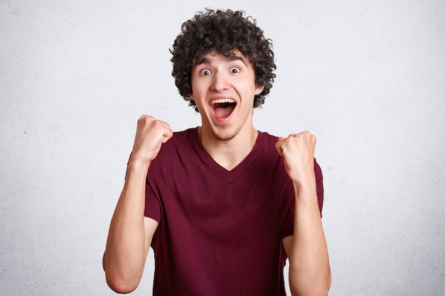 Emotivo onjoyed masculino adolescente aperta os punhos, tem cabelo escuro encaracolado, veste camiseta casual, posa em branco.