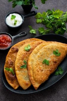 Empanadas caseiras com recheio e molho de tomate