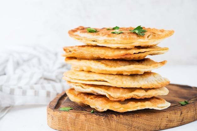 Empanadas caseiras fritas com carne de porco, chebureks com cogumelos em uma placa de madeira, close-up