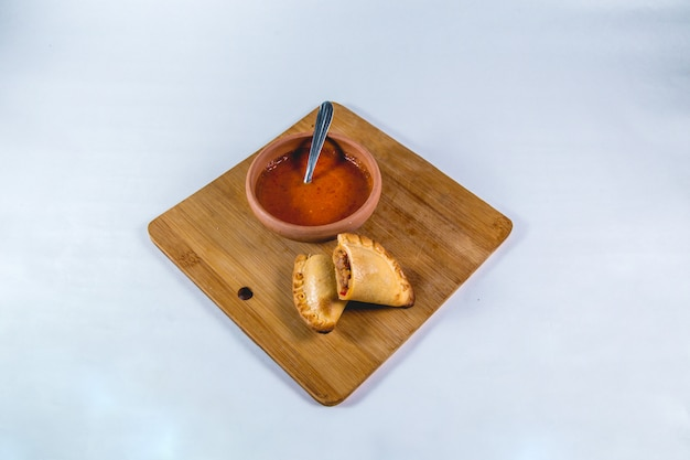 Empanadas e molho quente em uma mesa